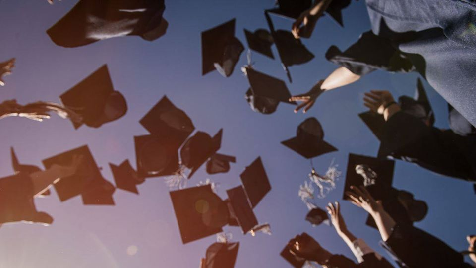 Graduate mortarboards tossed into the sky