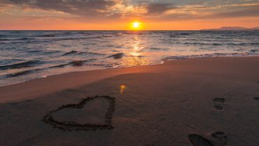 sunset beach with heart shape in sand